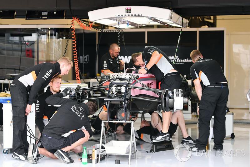 Mecánicos alrededor del VJM10 preparando el monoplaza en su garaje para los entrenamientos libres.