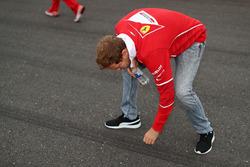 Sebastian Vettel, Ferrari walks the track and touches the asphalt