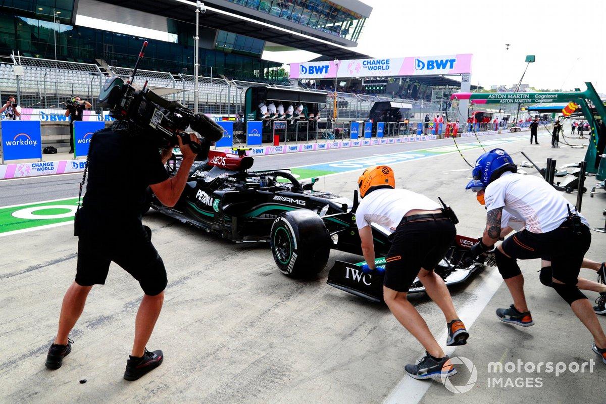 McLaren pit crew members attempt to assist Valtteri Bottas, Mercedes W12, in the pit lane