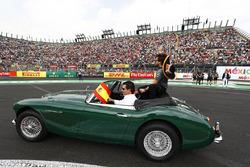 Fernando Alonso, McLaren, wears to fans from an Austin-Healey