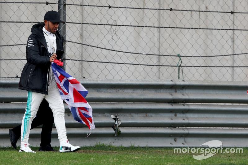 Lewis Hamilton, Mercedes AMG, attraversa la pista per intrattenere i tifosi e raccoglie una bandiera