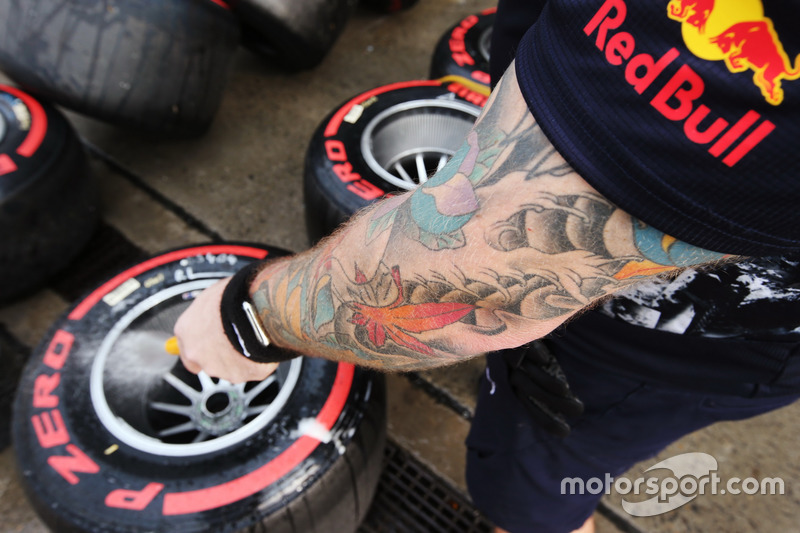 A Red Bull Racing mechanic washes some Super Soft tyres and rims