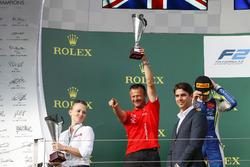 Prema team member celebrates on the podium with the winning team trophy