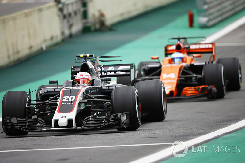 Kevin Magnussen, Haas F1 Team VF-17, Fernando Alonso, McLaren MCL32, en pit lane