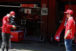 Sebastian Vettel, Ferrari, takes a picture of Kimi Raikkonen, Ferrari, on a vintage camera in the pits