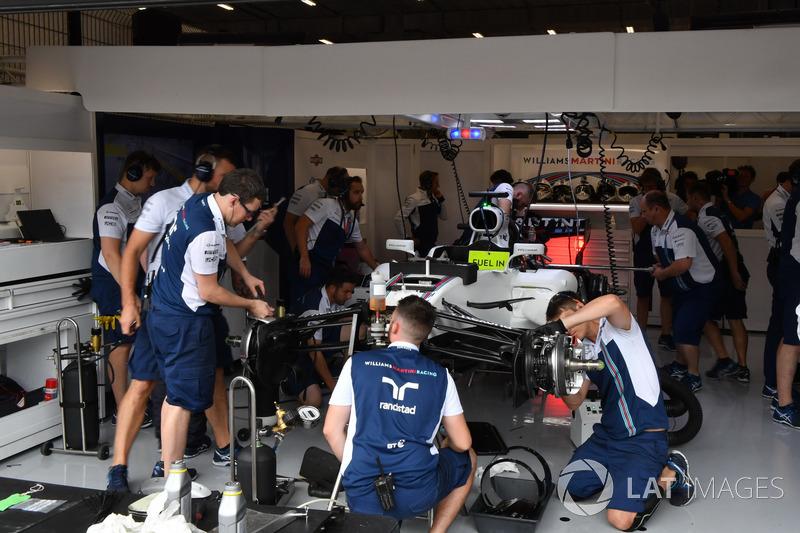Mechanics work on the car of Felipe Massa, Williams FW40 in the garage
