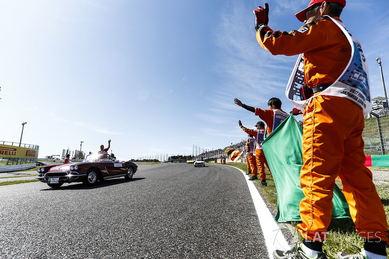 Marshals line the track as Sebastian Vettel, Ferrari, passes in the drivers parade