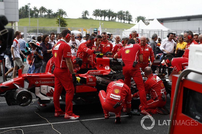 The Ferrari team work on the car of Kimi Raikkonen, Ferrari SF70H, after it developed a Turbo issue that caused a non-start for the driver