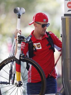 Sebastian Vettel, Ferrari, enters the paddock carrying a bicycle