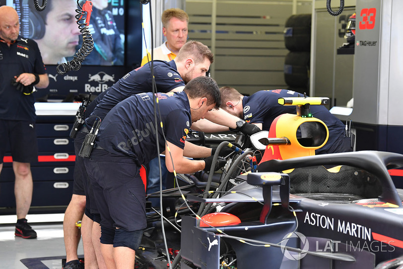 Red Bull Racing mechanics work on Red Bull Racing RB14 in the garage