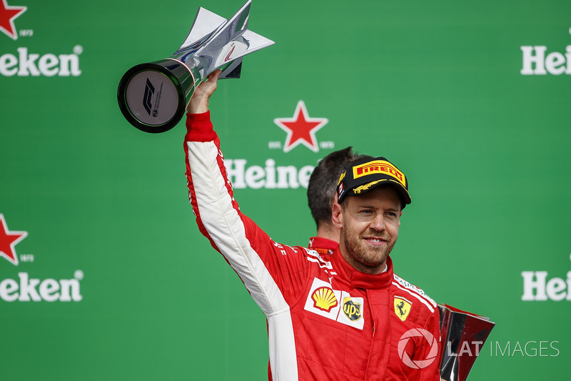 Sebastian Vettel, Ferrari, 1° classificato, sul podio con il trofeo
