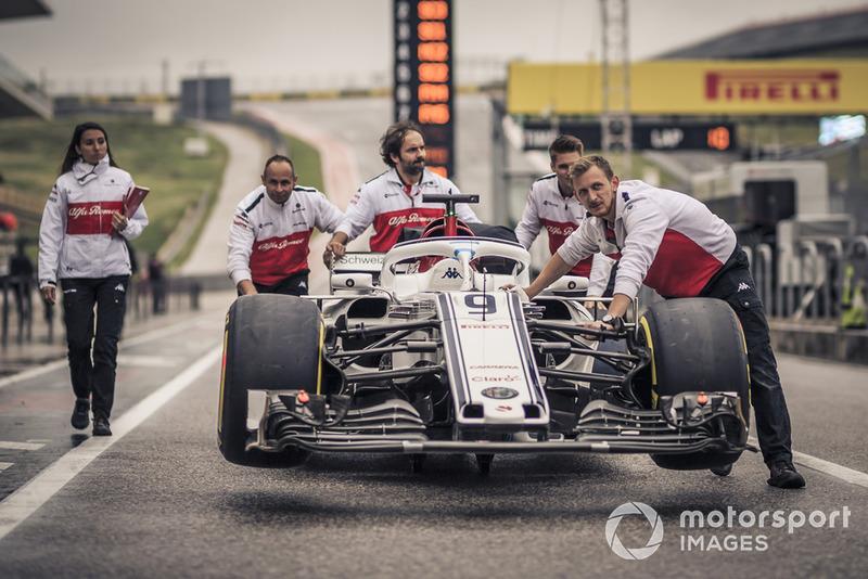 Des mécaniciens Alfa Romeo Sauber F1 Team avec une Alfa Romeo Sauber C37 dans la voie des stands