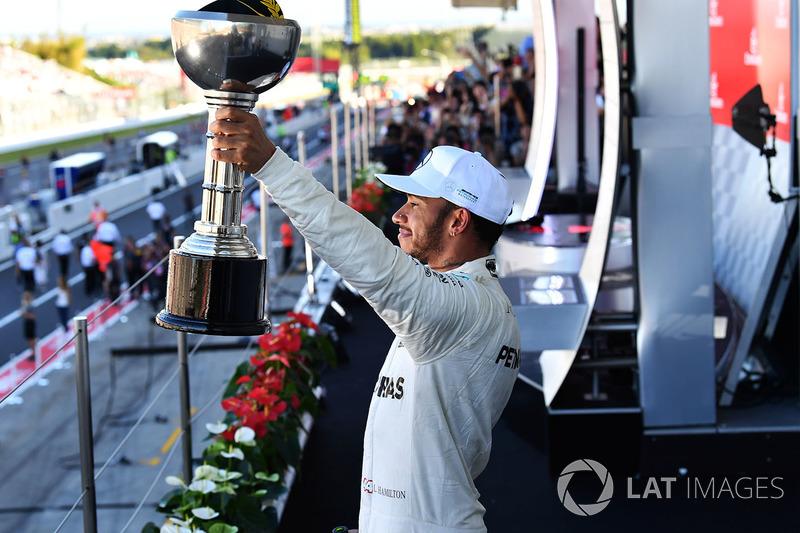 Il vincitore della gara Lewis Hamilton, Mercedes AMG F1 festeggia sul podio con il trofeo