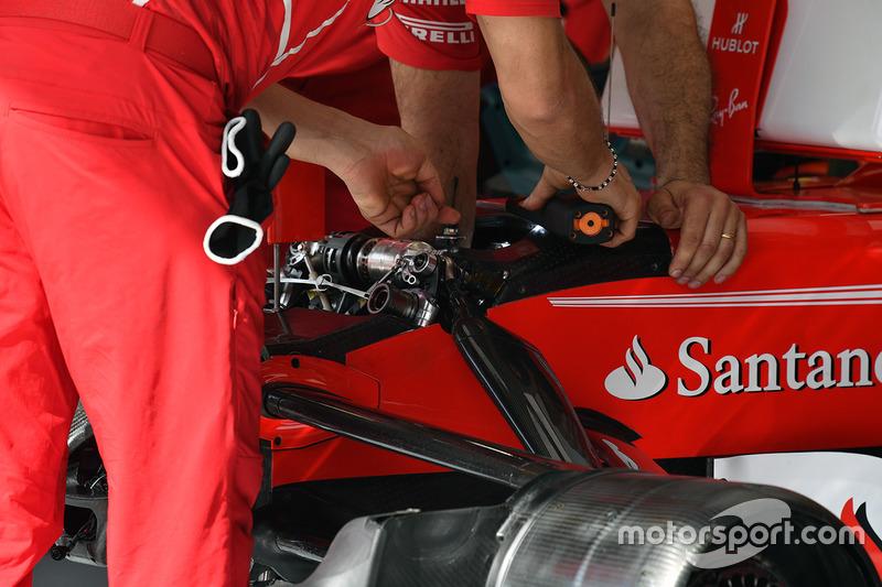 Los mecánicos de Ferrari realizando ajustes en la suspensión delantera del SF70H