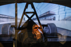 Fernando Alonso in the Honda Performance Development simulator while Gil de Ferran watches and is reflected in the control room window