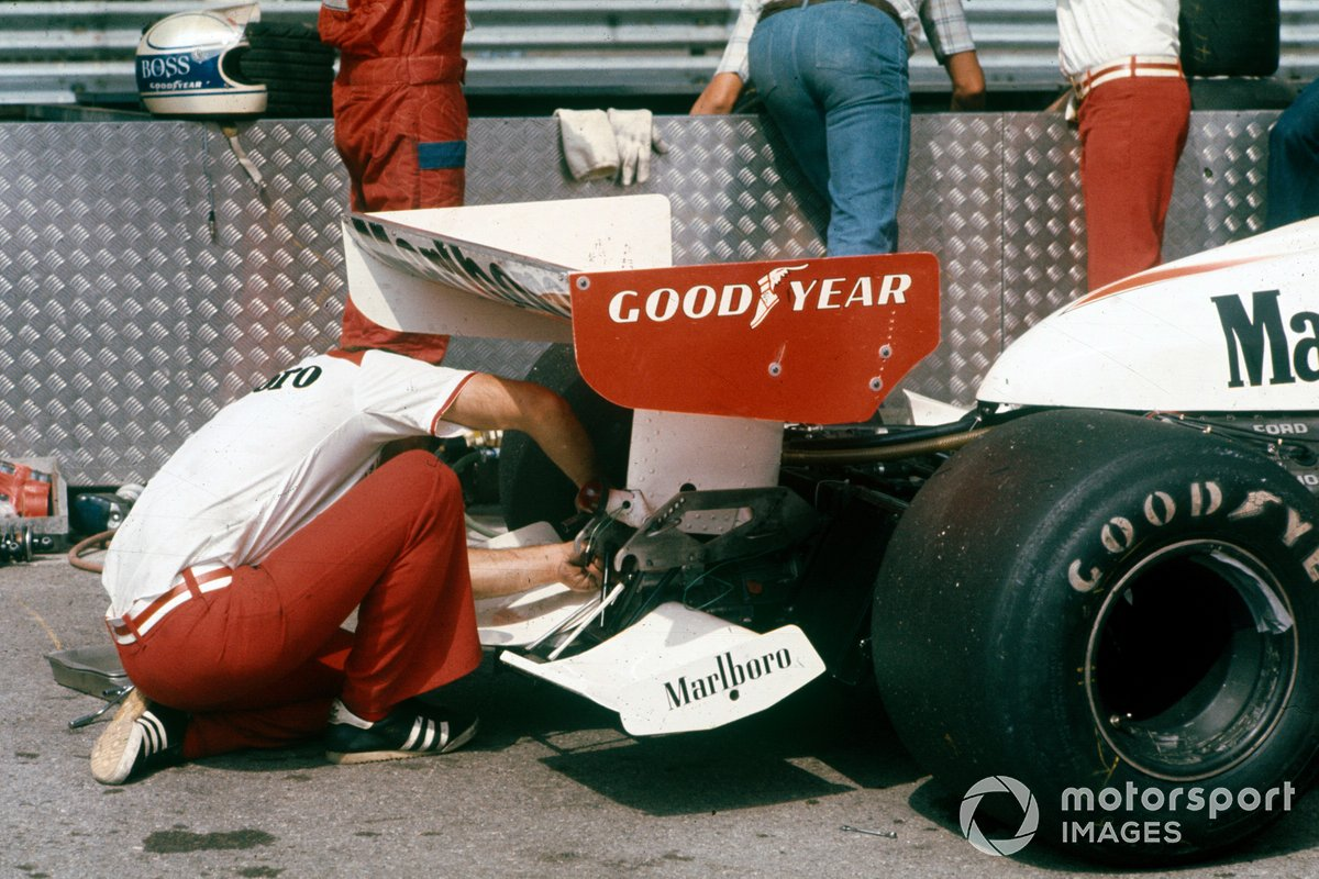 A mechanic works on the rear of the car of Jochen Mass, McLaren M23 Ford