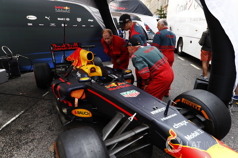 Rescue workers examine a Red Bull Racing under awnings