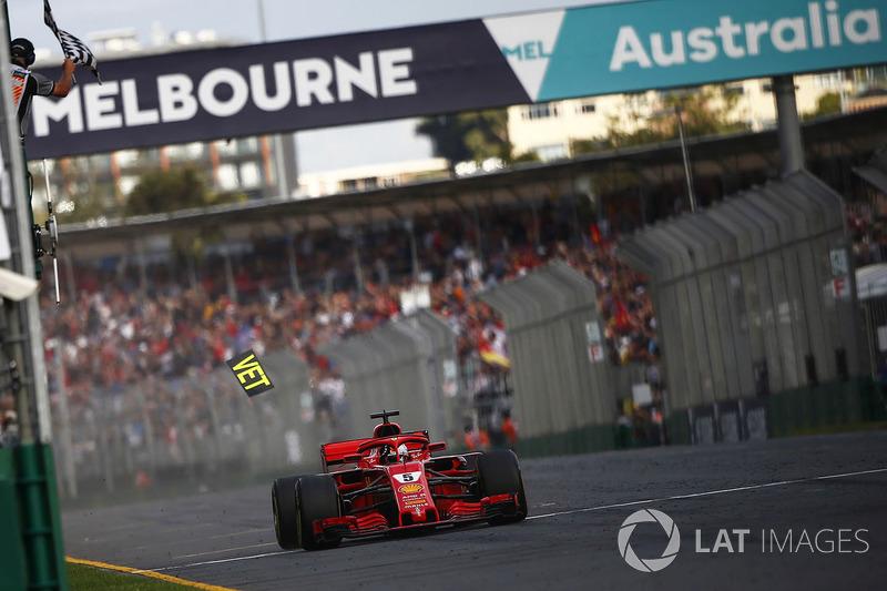 Sebastian Vettel, Ferrari SF71H, takes the chequered flag for victory as a piece of Ferrari pit boar