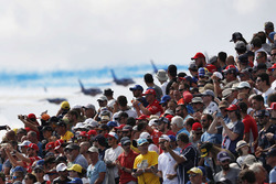 The crowd watches as the French Air Force Aerobatics team, La Patrouille de France, fly past in their Dassault Alpha Jet Es