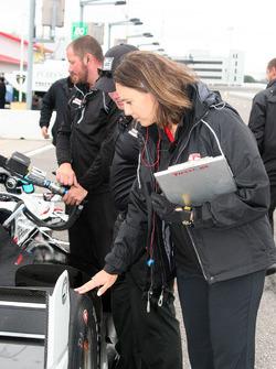 Cara Adams, ingeniero jefe para el Firestone Racing, inspecciona un neumático en Josef Newgarden, co