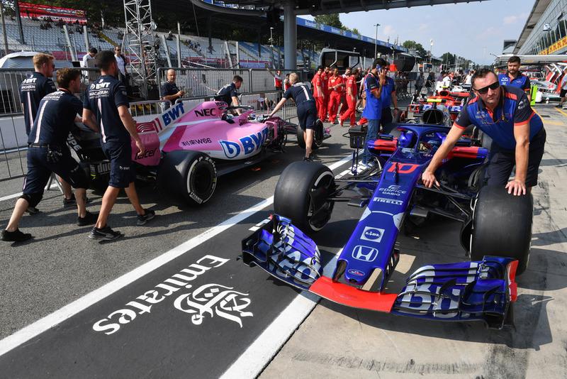 Toro Rosso crew members push the car