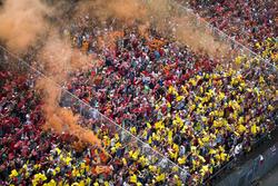 Las antorchas de humo naranja se encienden en una tribuna de fans