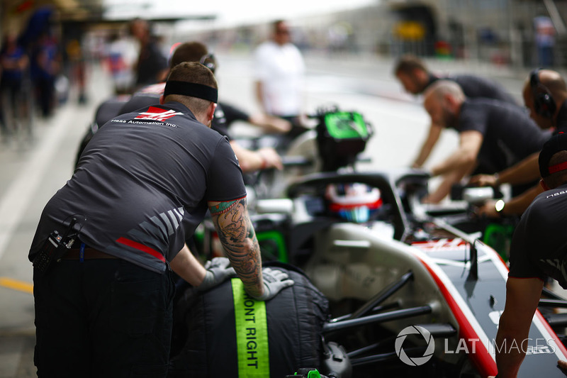 Haas engineers with Romain Grosjean, Haas F1 Team VF-18 Ferrari, in the pit lane