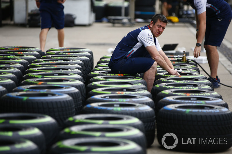 A Williams team member works on Pirellii tyres