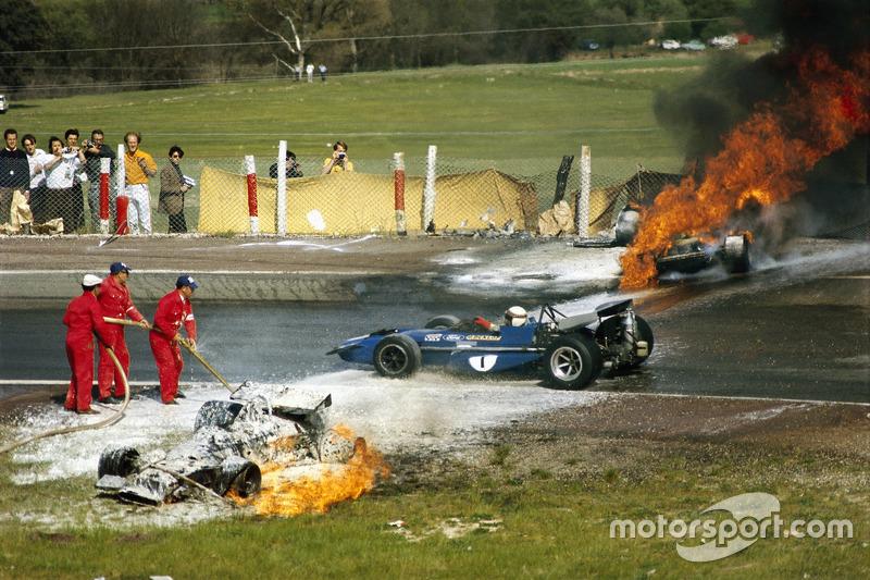1970 - Jackie Stewart melewati dua bangkai mobil yang sebelumnya dikemudikan Jackie Oliver, BRM dan Jacky Ickx, Ferrari
