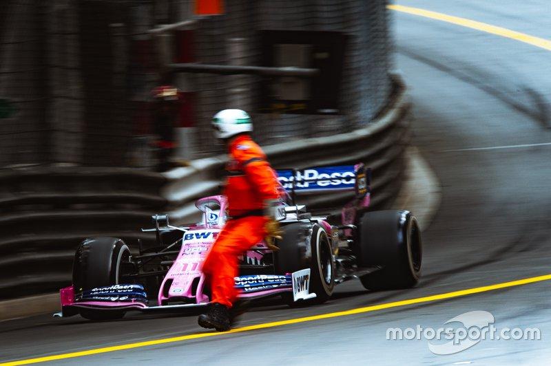 Oficial se cruza la pista por el frente del coche de Sergio Pérez
