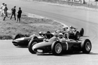 Phil Hill, Ferrari Dino 156, takes a wide line through Tarzan Corner while Trevor Taylor, Lotus 24-Climax, Ricardo Rodriguez, Ferrari Dino 156, and Jack Brabham, Lotus 24-Climax, are on the inside