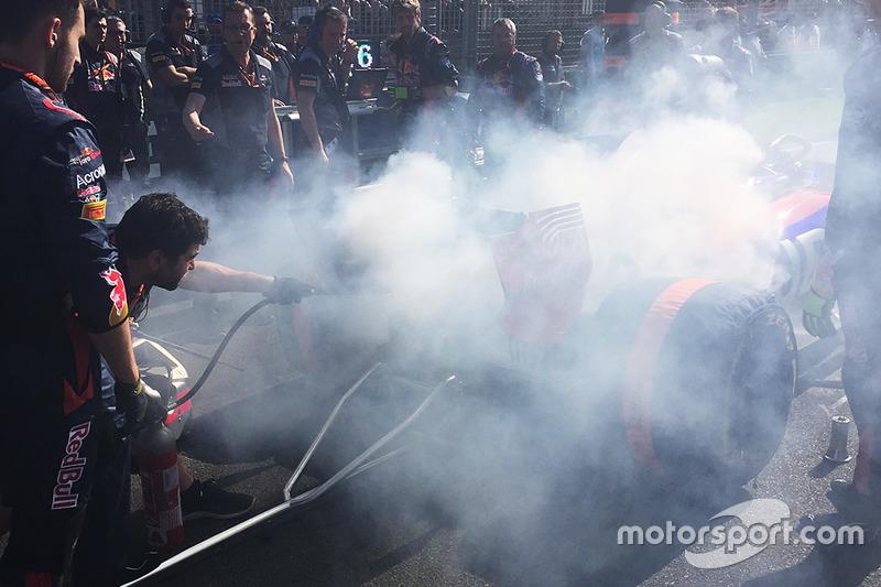 Miembros del equipo utilizan un extintor en el coche de Daniil Kvyat, Scuderia Toro Rosso después de un incendio