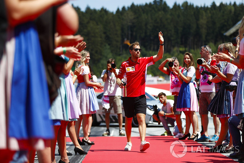 Sebastian Vettel, Ferrari, waves as he passes through lines of grid girls