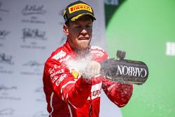 El ganador de la carrera Sebastian Vettel, Ferrari, celebra con champagne en el podio