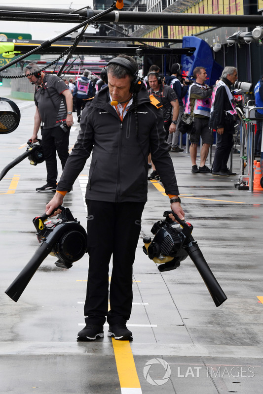 McLaren mechanic dries the pit box
