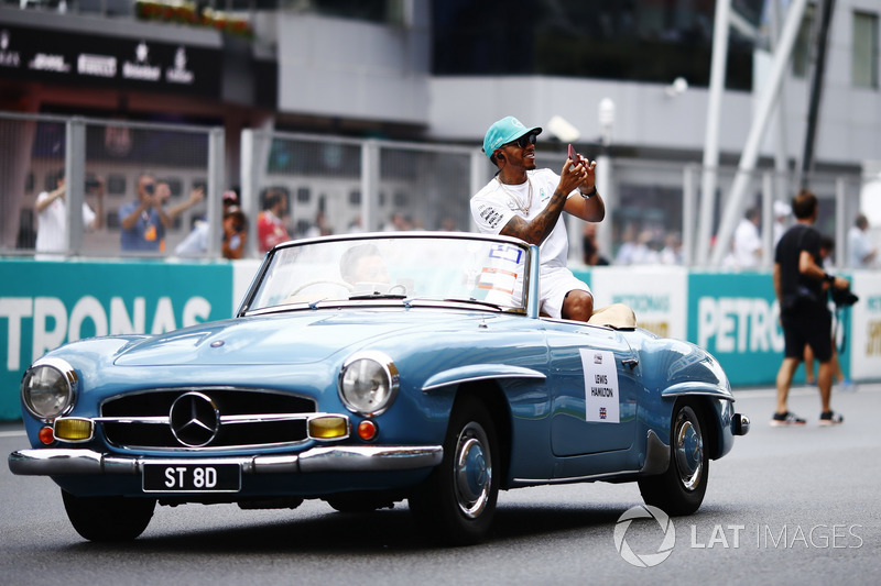 Lewis Hamilton, Mercedes AMG F1, waves from a Mercedes 190SL on the drivers parade