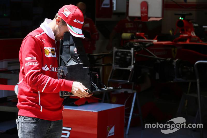 Sebastian Vettel, Ferrari, tries out a vintage camera in the pits