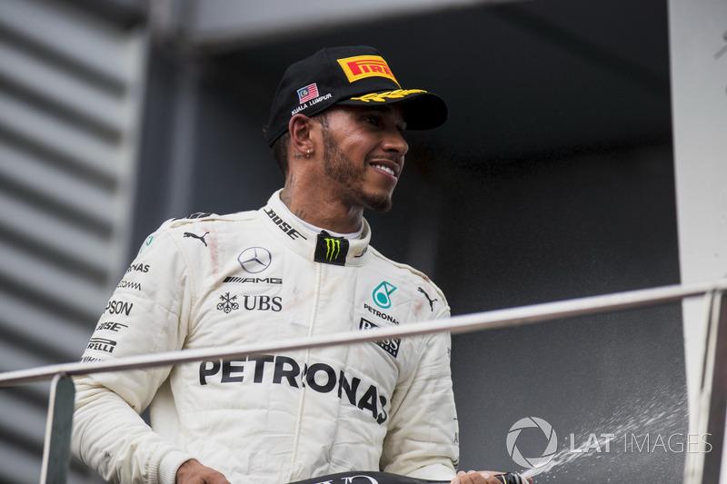 Друге місце Льюіс Хемілтон, Mercedes AMG F1, розпилює шампанське на подіумі