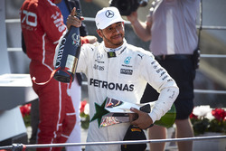 Race winner Lewis Hamilton, Mercedes AMG F1, leaves the podium, his trophy and Champagne