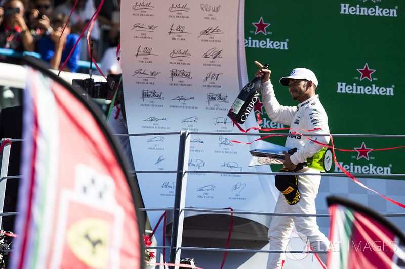 Race winner Lewis Hamilton, Mercedes AMG F1, leaves the podium, his trophy and Champagne bottle