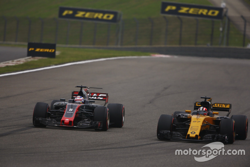 Romain Grosjean, Haas F1 Team VF-17, passes Nico Hulkenberg, Renault Sport F1 Team RS17
