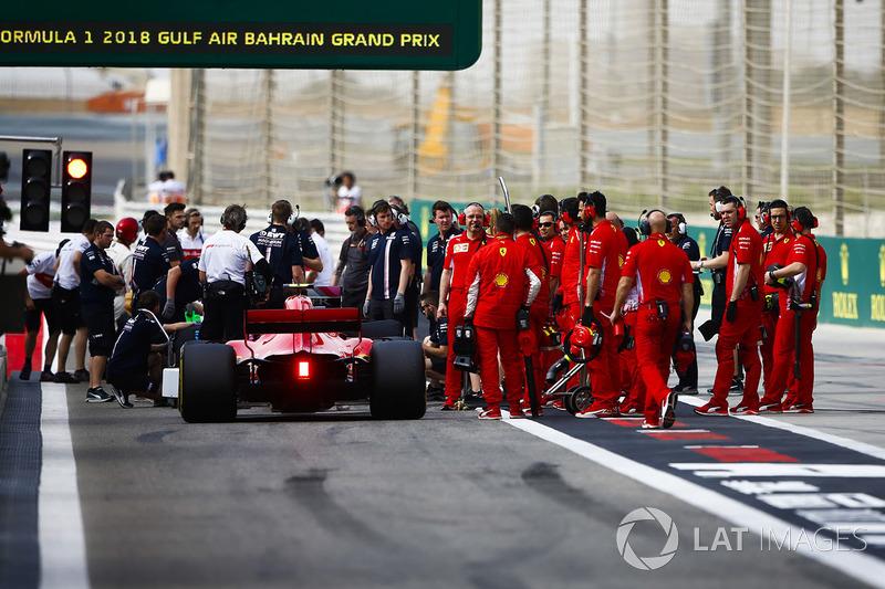 Kimi Raikkonen, Ferrari SF71H, and Ferrari engineers near the pit lane exit