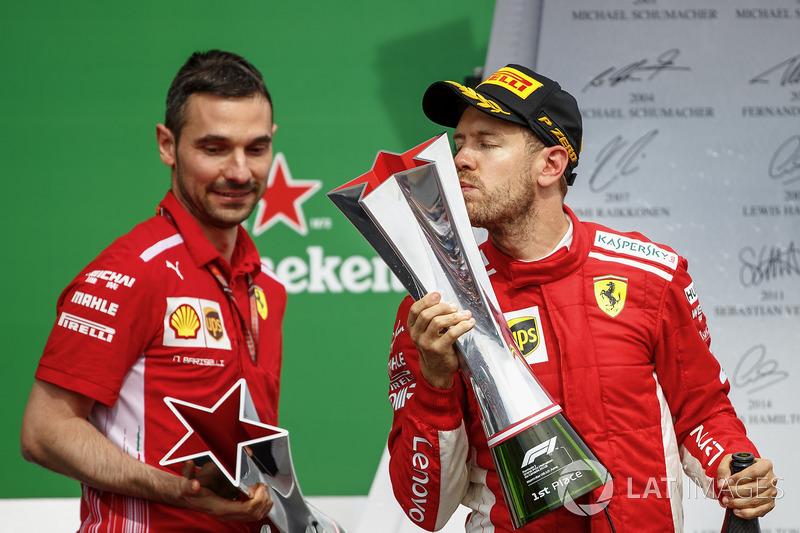 Sebastian Vettel, Ferrari, 1st position, kisses his trophy on the podium alongside Nicola Bariselli,