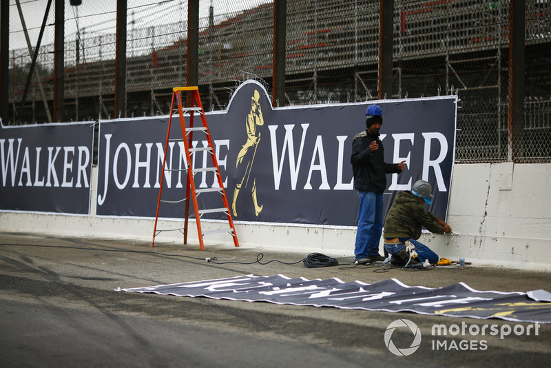 Workmen apply the final touches to a Johnnie Walker advertising sign