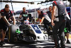 Mechanics attend to Romain Grosjean, Haas F1 Team, in his pit box