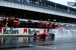 Winnaar Michael Schumacher, Ferrari F310 passeert de finishvlag