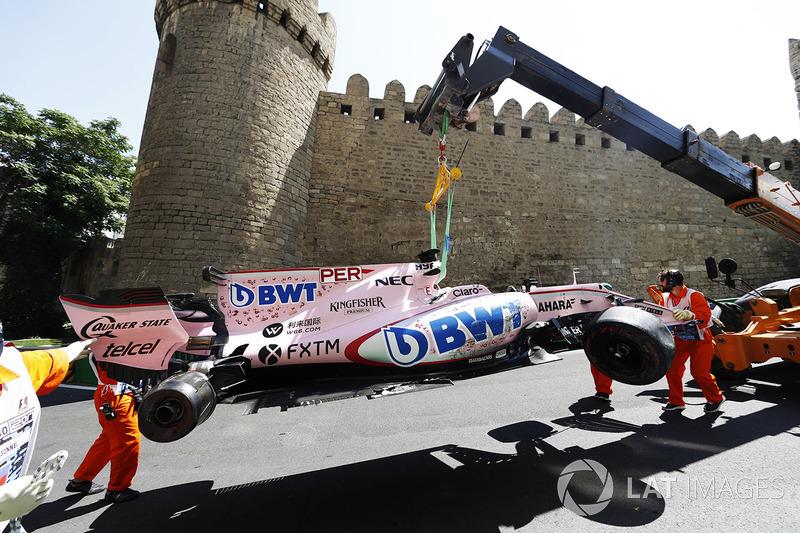 Oficiales de pista remueven el coche chocado de Sergio Pérez Sahara Force India F1 VJM10, en una grúa