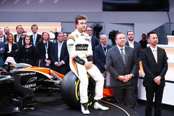 Fernando Alonso, McLaren, sits on a front wheel of the MCL32, alongside Zak Brown, Executive Director of McLaren Technology Group, and Yusuke Hasegawa, Senior Managing Officer, Honda