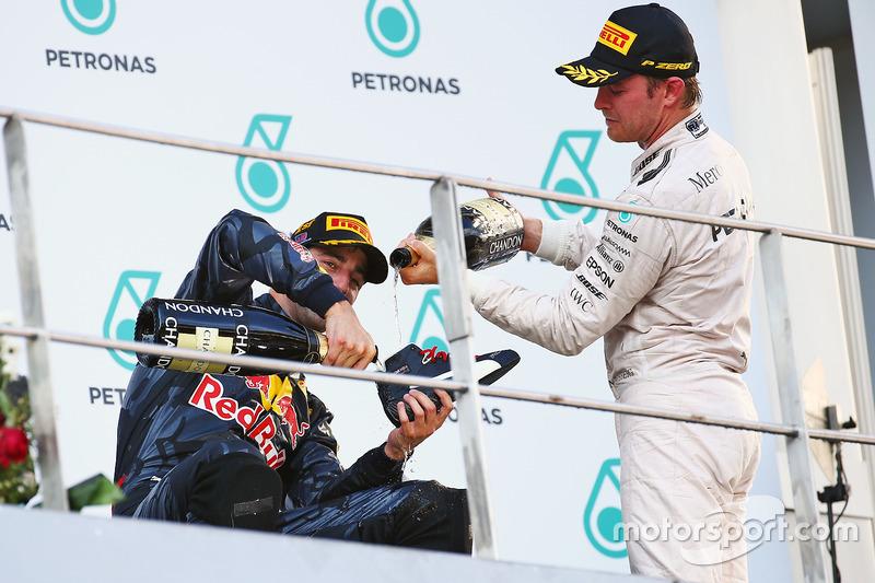 Race winner Daniel Ricciardo, Red Bull Racing celebrates on the podium with Nico Rosberg, Mercedes AMG F1 with his race boot