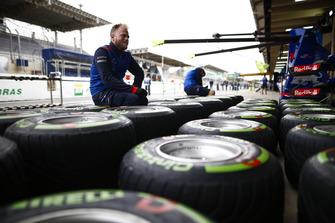 Un meccanico Toro Rosso al lavoro su degli pneumatici Pirelli